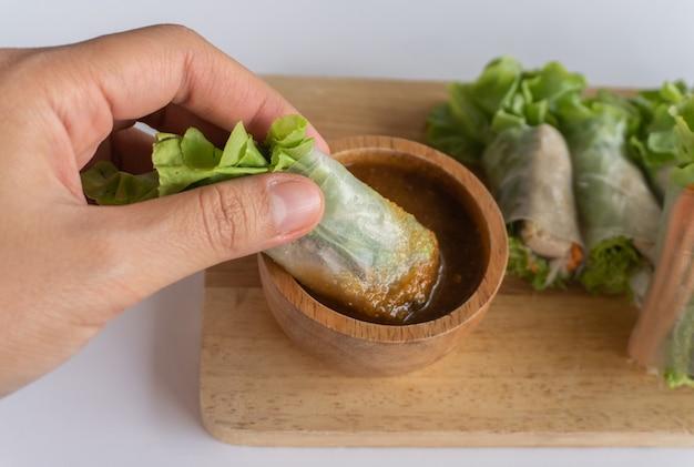 Dłoń trzymająca roladkę sałatkową i dip w sosie z owoców morza, makrela salad roll na desce do krojenia i sos z owoców morza na drewnianej misce, salad roll to popularne potrawy uliczne w tajlandii i dobre danie dietetyczne.