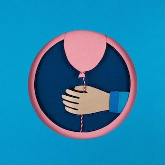 Dłoń trzymająca różowe balony papierowe w niebieskim okrągłym otworze nakładającym się na siebie, rama koło.