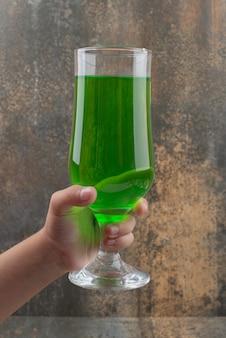 Dłoń trzymająca s szklankę soczystej zielonej lemoniady na powierzchni marmuru