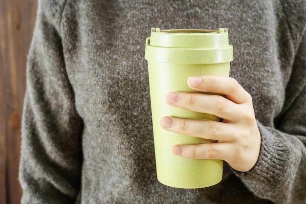 Dłoń trzymająca się za ręce wielokrotnego użytku eko kubek kawy