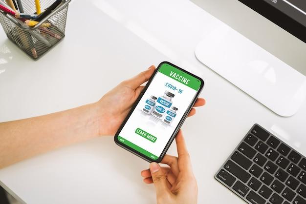 Dłoń trzymająca smartfona i wyświetlająca stronę internetową szczepionki koronowej online z przyciskiem dowiedz się więcej.