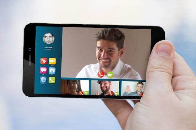 Dłoń trzymająca spotkanie wideokonferencji na ekranie smartfona. grafika ekranu jest zmyślona.