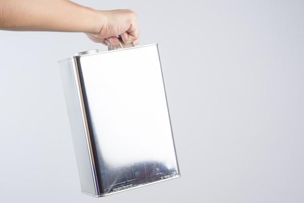 Dłoń trzymająca stalowy lub nierdzewny kwadratowy puszkę z chemicznej blachy
