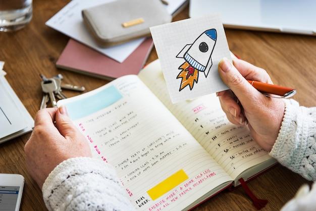 Dłoń trzymająca start rakietowy rysunek na notatkę