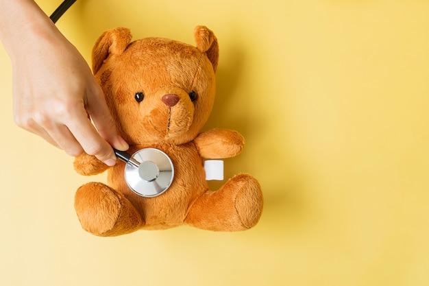 Dłoń trzymająca stetoskop na lalce bear do wspierania życia i choroby dziecka. wrzesień miesiąc świadomości raka u dzieci, koncepcja opieki zdrowotnej i ubezpieczenia na życie