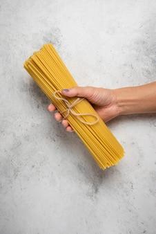 Dłoń trzymająca surowe spaghetti na białej powierzchni.