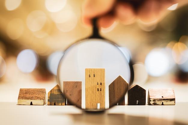 Dłoń trzymająca szkło powiększające i patrząc na model domu,