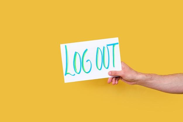 Dłoń trzymająca tabliczkę z odręcznym napisem log out