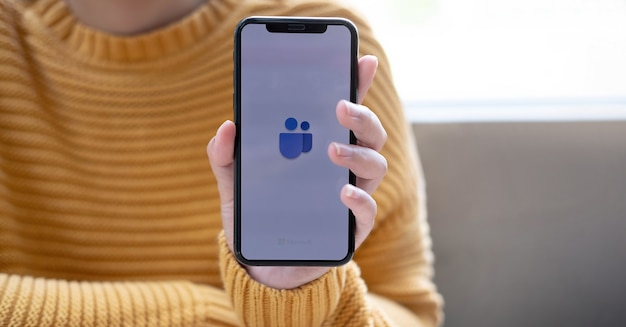 Dłoń trzymająca telefon komórkowy z ikoną dwóch osób