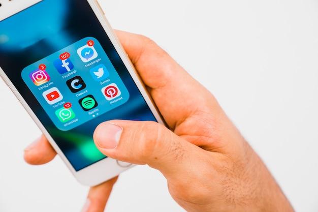 Dłoń trzymająca telefon z aplikacjami