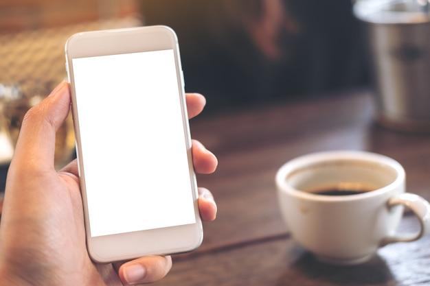 Dłoń trzymająca telefon z pustym ekranem i filiżankę kawy na drewnianym stole w trybie