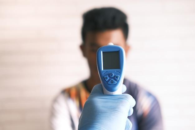 Dłoń trzymająca termometr na podczerwień do pomiaru temperatury