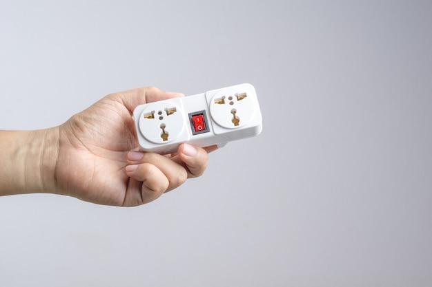Dłoń trzymająca uniwersalną wtyczkę adaptera podróżnego z wyłącznikiem zasilania