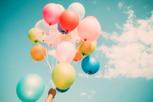 Dłoń trzymająca wielokolorowe balony wykonane w retro vintage efekt filtra instagram.