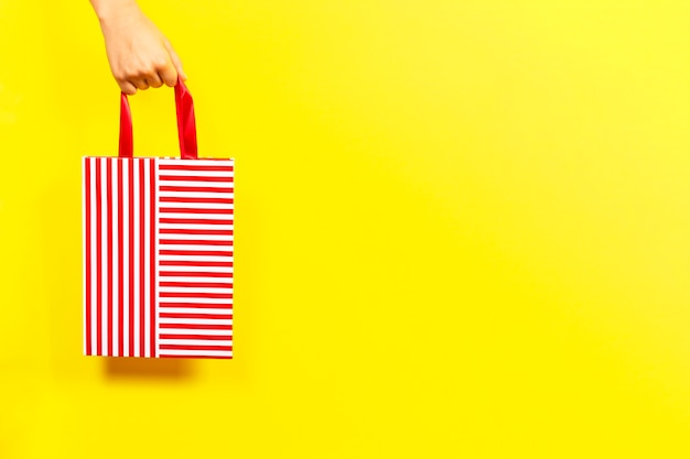 Dłoń trzymająca worek na prezent w czerwone paski