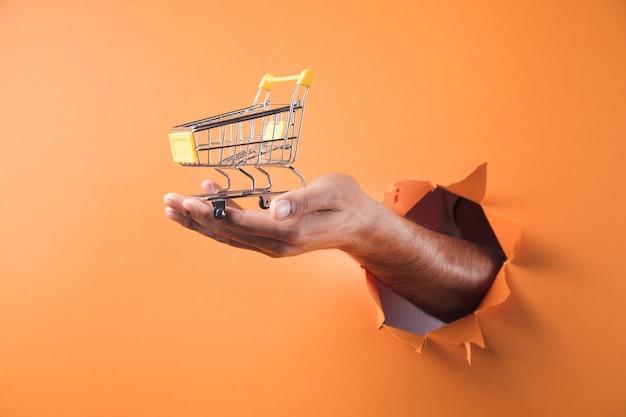 Dłoń trzymająca wózek na pomarańczowym tle