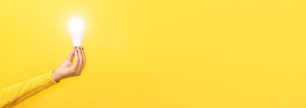 Dłoń trzymająca żarówkę, oświetlona żarówka na żółtej przestrzeni