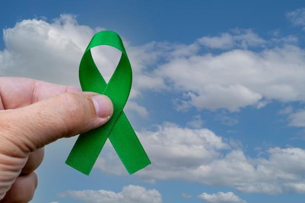 Dłoń trzymająca zieloną wstążkę do wspierania osób z rakiem nerki i problemami ze zdrowiem psychicznym.