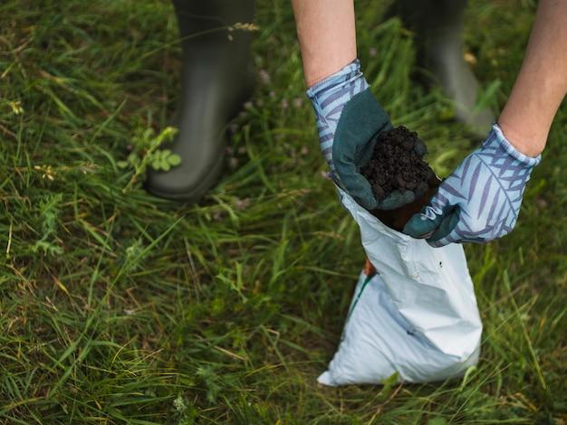 Dłoń trzymająca ziemię z paczki