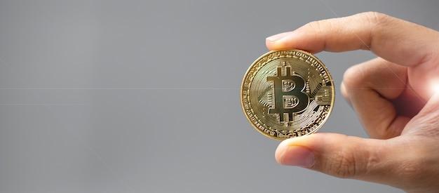Dłoń trzymająca złotą monetę kryptowaluty bitcoin.