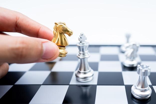 Dłoń trzymająca złoty atak konia srebrny król w bitwie na szachownicy.