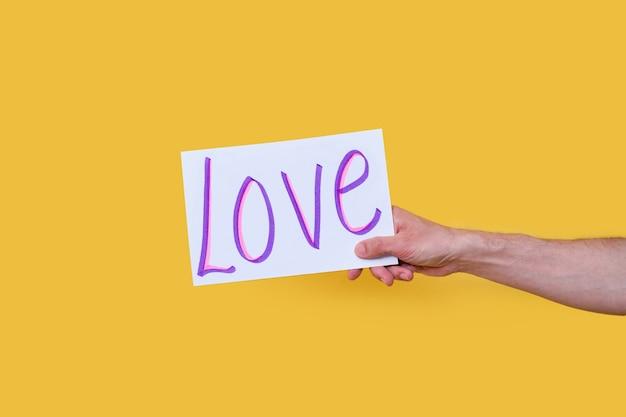 """Dłoń trzymająca znak z napisem """"miłość"""" napisanym pismem na na białym tle"""