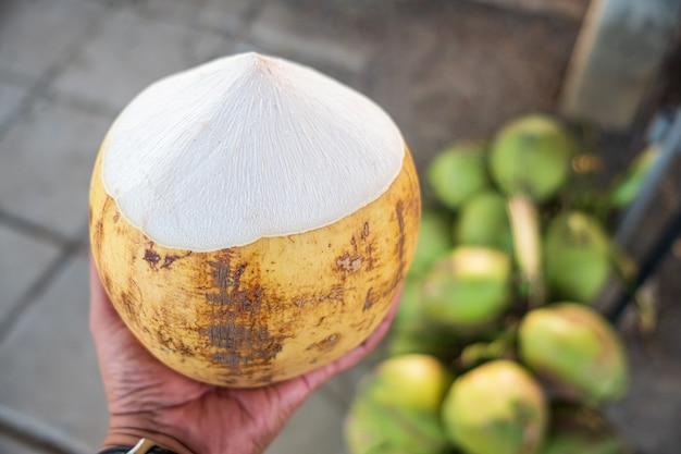 Dłoń trzymająca żółtego kokosa