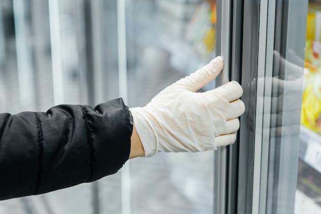 Dłoń w białej rękawiczce otwiera drzwi do witryny. bezpieczeństwo epidemiczne