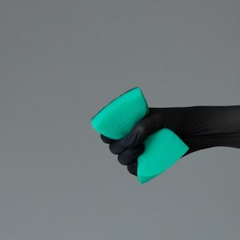 Dłoń w gumowej rękawicy posiada kolorową gąbkę do mycia na neutralnym tle.