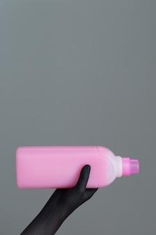 Dłoń w gumowej rękawicy zawiera butelkę detergentu