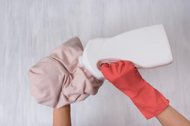Dłoń w rękawicy wylewa płyn do prania odzieży. zbliżenie