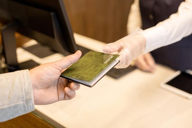 Dłoń w rękawiczce młodej recepcjonistki stojącej przed komputerem i przekazującej paszport gościowi hotelu przez ladę recepcyjną