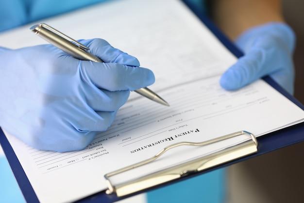 Dłoń w rękawiczce trzyma podkładkę i długopis i wypełnia formularz rejestracyjny pacjenta