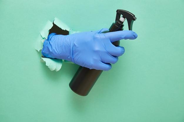 Dłoń w rękawiczce trzyma środek dezynfekujący w czarnej butelce z rozpylaczem. zielonego papieru tło z poszarpaną dziurą
