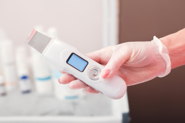 Dłoń w rękawiczce trzymająca skrobak ultradźwiękowy. kosmetologia medyczna. terapia ultradźwiękowego oczyszczania skóry. salon spa.
