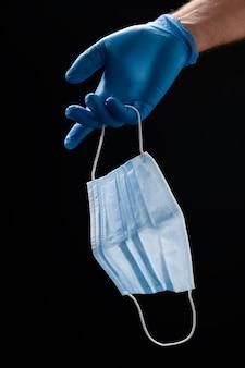 Dłoń w rękawiczkach trzyma maskę medyczną twarzy na czarno