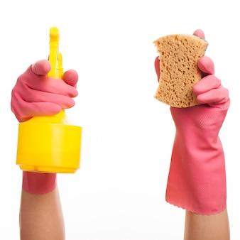 Dłoń w różowej rękawicy trzymającej spray i gąbkę