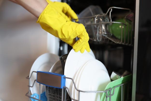 Dłoń w żółtej rękawiczce wyjmij umyte naczynia kuchenne