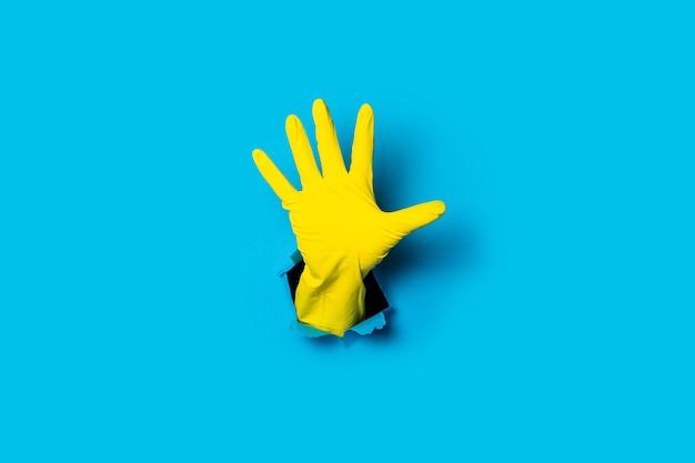 Dłoń w żółtej rękawiczce z otwartą dłonią, pięć palców na jasnoniebieskim tle