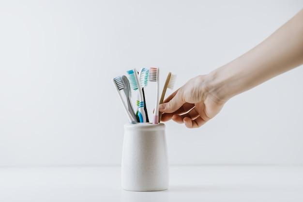 Dłoń wyjmuje przyjazną dla środowiska szczoteczkę do zębów z białej filiżanki