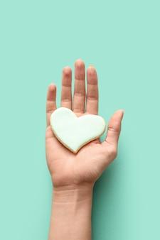 Dłoń z ciastkiem w kształcie serca na turkusie