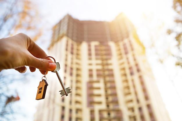 Dłoń z kluczem i drewniany brelok-domek. tło wielomieszkaniowy wieżowiec. budowa, przeprowadzka do nowego mieszkania, hipoteka, wynajem i zakup nieruchomości. aby otworzyć drzwi. skopiuj miejsce