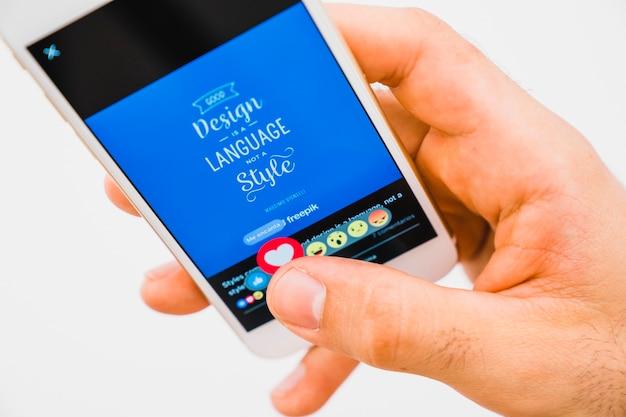 Dłoń z telefonu, naciskając przycisk podobny w facebooku