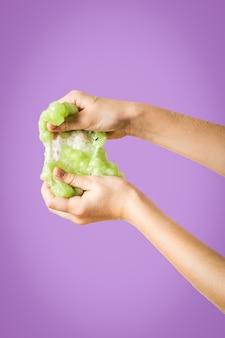 Dłonie dziecka rozciągają się w kolorze limonkowej zieleni na liliowym tle. zabawka antystresowa. zabawka do rozwoju motoryki ręcznej.