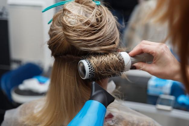 Dłonie fryzjera suszy blond włosy suszarką i okrągłą szczotką