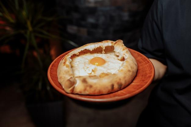 Dłonie kelnera w czarnych rękawiczkach trzymają dwa tradycyjne chaczapuri z serem i jajkiem.