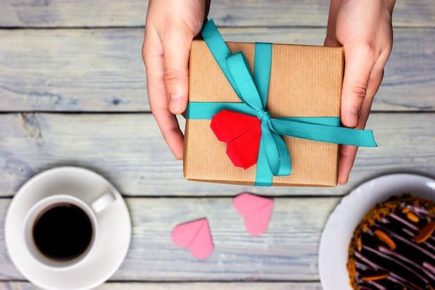 Dłonie kobiet dają prezent zawinięty w papier rzemieślniczy i przewiązany świąteczną wstążką.