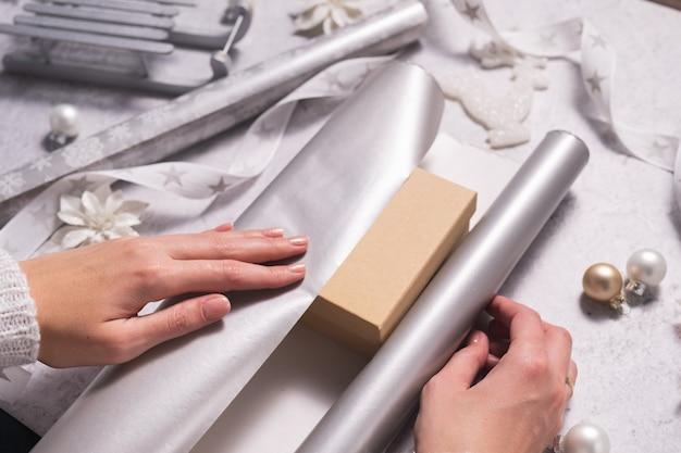 Dłonie kobiety owijają prezent świąteczny w srebrny papier pakowy święta bożego narodzenia