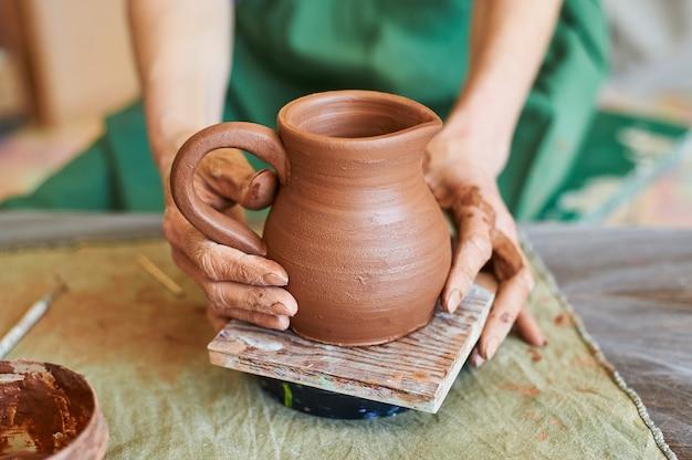 Dłonie kobiety potter w zielonym fartuchu pokazują gliniany dzbanek, który wykonała.