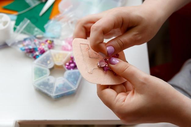 Dłonie kobiety wykonują ozdobę broszki z różowych koralików i kryształków